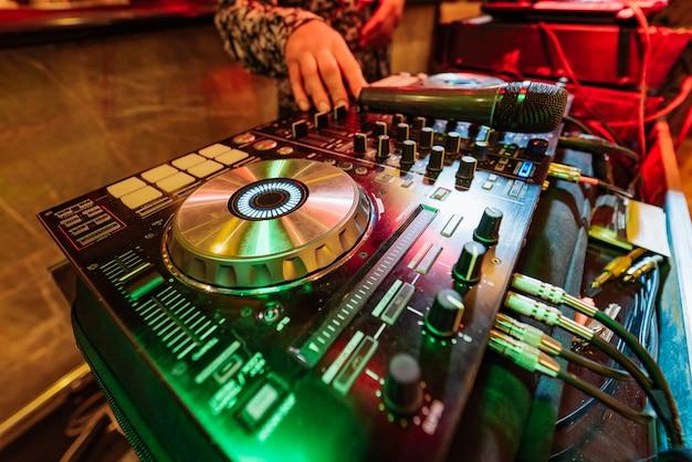 As mãos do dj misturam a faixa no console no clube na noite