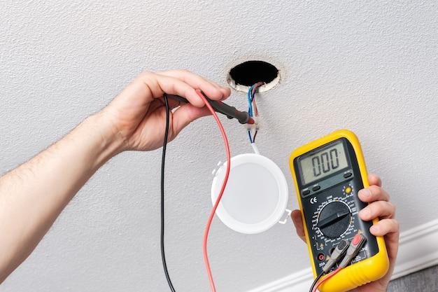 As mãos do eletricista verificam a fonte de alimentação do testador antes de instalar a luz led