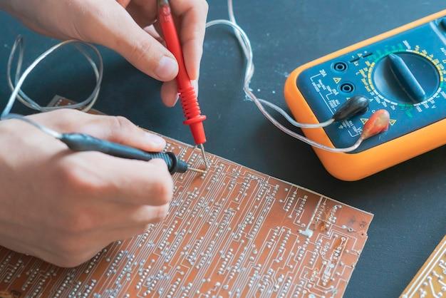 As mãos do engenheiro medem a corrente de tensão na placa eletrônica