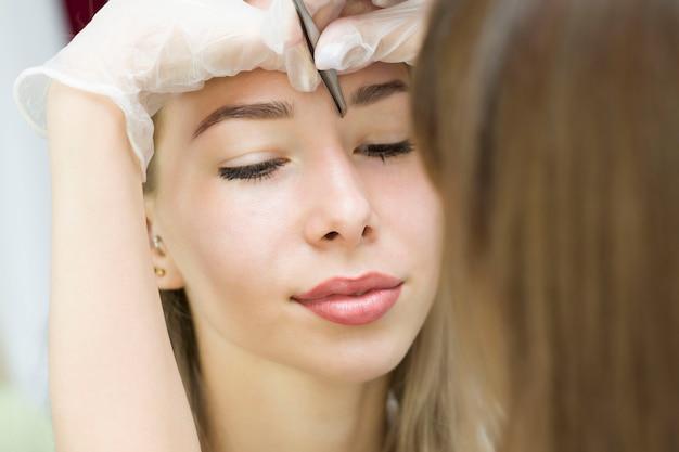 As mãos do estilista em luvas brancas arrancam suas sobrancelhas com uma pinça. um lindo rosto feminino atraente de uma mulher ou senhora bem tratada de cabelos louros. modelagem e laminação de sobrancelhas.