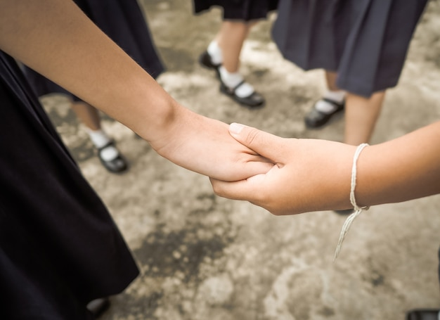 As mãos do estudante do ensino médio segurar juntos.