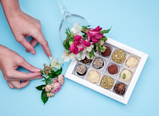 As mãos do florista decoram com flores uma caixa de chocolates artesanais de cho branco
