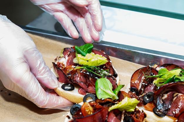 As mãos do garçom nas luvas seguram um sanduíche de carne. catering para eventos.