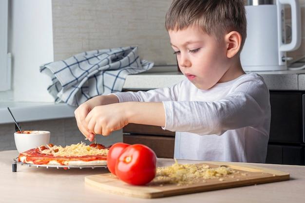 As mãos do garoto polvilhe o queijo na massa de pizza. processo de cozinhar pizza caseira por criança. habilidades pré-escolares, ajudante. lazer em família. ruído artificial, foco seletivo, luz de fundo
