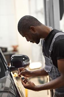 As mãos do homem africano usam o pincel de detalhes para pintar carros ou para limpar e remover a sujeira