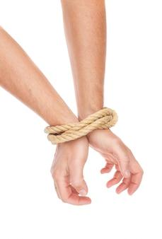 As mãos do homem amarradas com uma corda. limitação de ações.