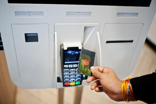 As mãos do homem cliente na loja fazem pedidos e pagam com cartão de crédito sem contato através do quiosque de piso auto-pago para fast-food, terminal de pagamento. pay pass.