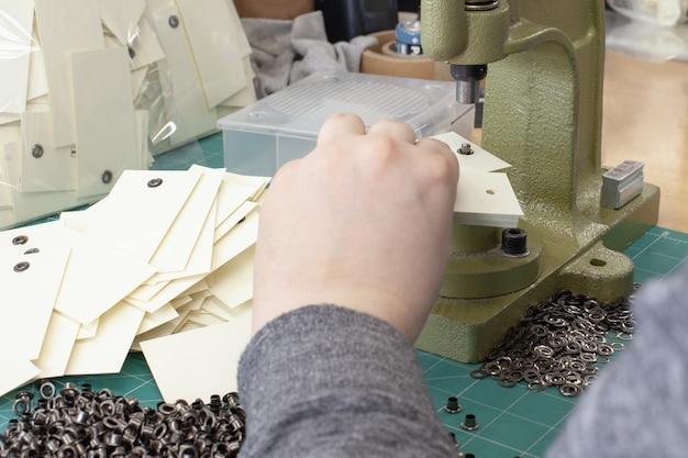 As mãos do homem colocam ilhós e ilhós em etiquetas de roupas em uma grande máquina de ilhós profissional portátil