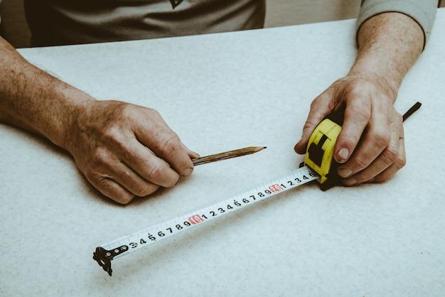 As mãos do homem de funcionamento idoso com lápis e roleta fecham-se acima.