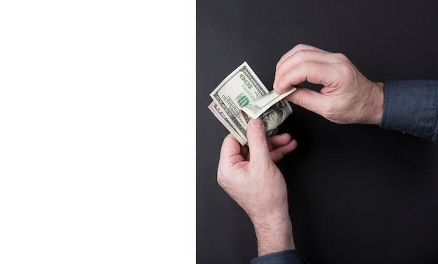 As mãos do homem de negócios funcionam pelo dinheiro. conte os dólares.
