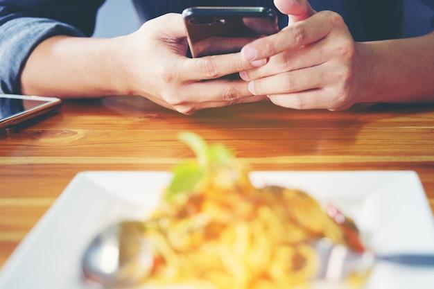 As mãos do homem do close-up usam o dedo apontando o telefone esperto do móvel na mesa do alimento