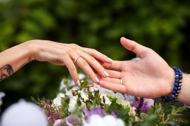 As mãos do homem e da mulher tocam-se mutuamente sobre um buquê
