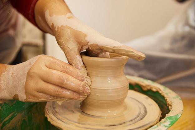 As mãos do homem estão moldando um vaso em um local de trabalho de cerâmica