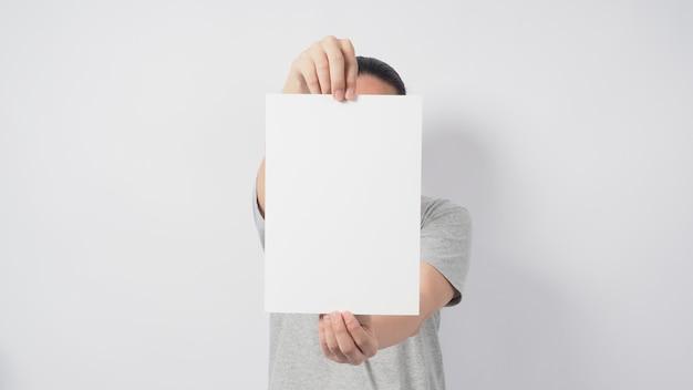 As mãos do homem estão segurando o papel a4 e usam camiseta cinza e em pé sobre um fundo branco.