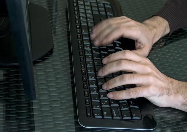 As mãos do homem fecham-se no teclado