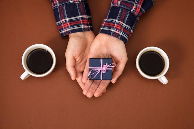 As mãos do homem mantêm o presente da caixa perto de duas xícaras de café em marrom.