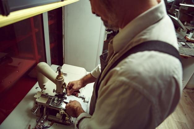 As mãos do homem por trás da costura. oficina de couro. têxtil vintage industrial. o homem na profissão feminina. conceito de igualdade de gênero