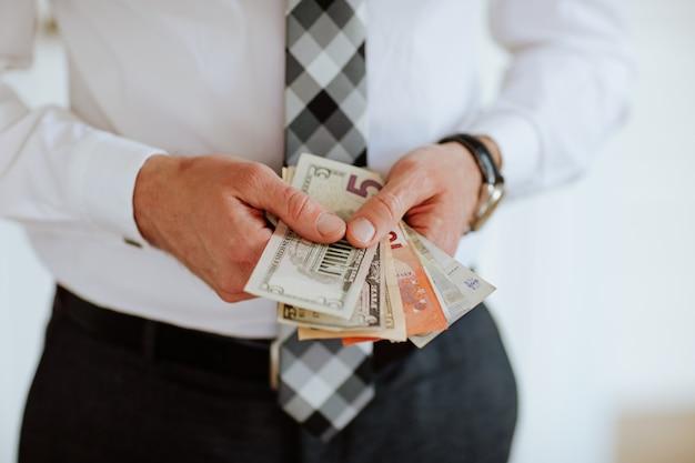 As mãos do homem segurando dinheiro como euros e dólares em fundo branco.