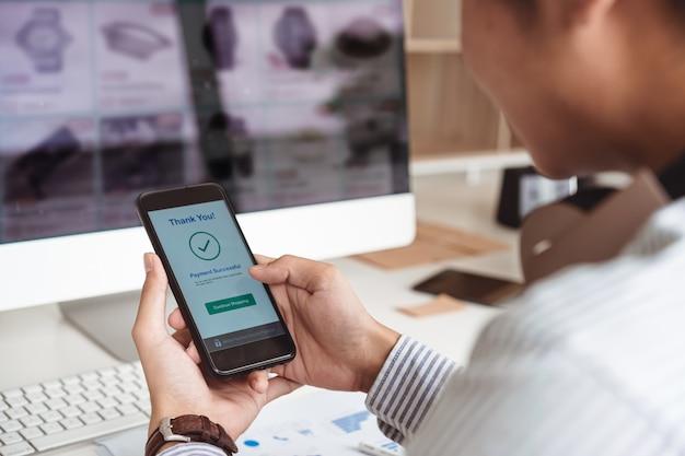 As mãos do homem segurando o smartphone e pagamento on-line bem sucedido. conceito de pagamento de carteira móvel.
