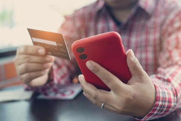 As mãos do homem segurando um cartão de crédito e usando o telefone inteligente para fazer compras online. cartão de crédito para pagar e fazer compras online. conceito de pagamento online. freelancer na cafeteria e trabalhando.