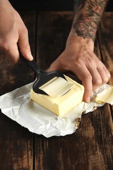 As mãos do homem tatuado usam uma faca especial para picar uma fatia bem fina de manteiga, tudo em uma mesa de madeira rústica