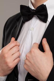 As mãos do homem tocam gravata borboleta