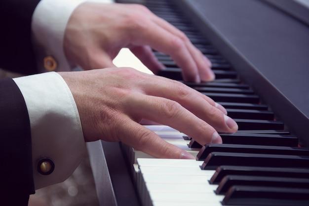As mãos do homem tocando em um piano no concerto