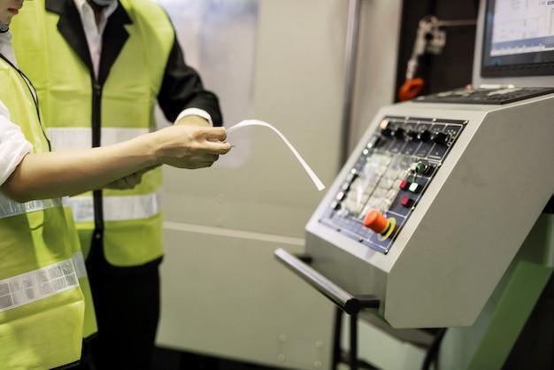 As mãos do inspetor de fábrica verificam o modelo de renderização da máquina de torno cnc para auditoria interna