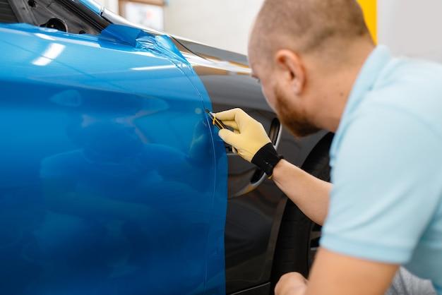 As mãos do invólucro do carro instalam folha de vinil ou filme
