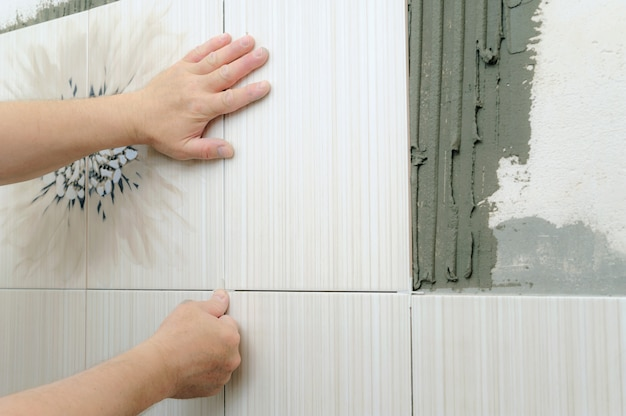 As mãos do ladrilhador estão instalando uma telha cerâmica.