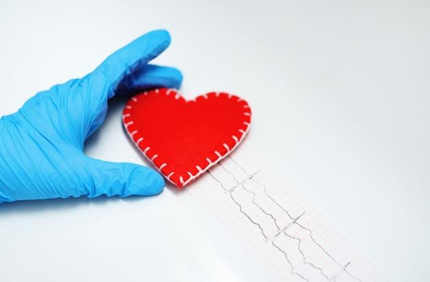 As mãos do médico em luvas de borracha azul contra um coração vermelho e um cardiograma de papel. o conceito de prevenção de doenças cardiovasculares