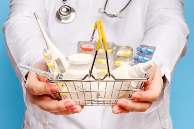 As mãos do médico estão segurando o carrinho de compras com várias pílulas e comprimidos