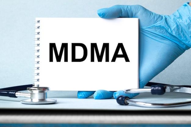 As mãos do médico mostram a palavra mdma.