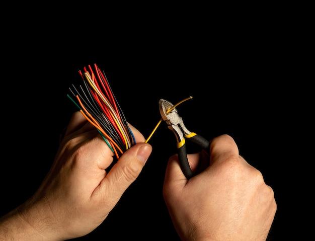 As mãos do mestre seguram o alicate e o close do fio