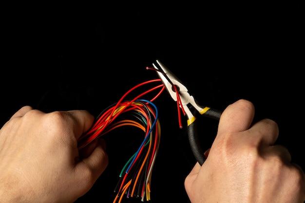 As mãos do mestre seguram um alicate diagonal e fio
