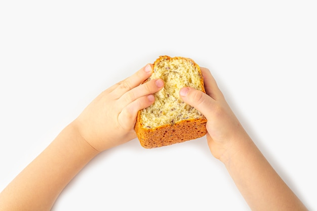 As mãos do miúdo guardam o pão integral caseiro recentemente cozido no fundo branco com espaço da cópia para o texto. conceito de comida orgânica e vegetariana.