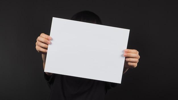 As mãos do modelo feminino estão segurando um papel a4 em branco sobre fundo preto.