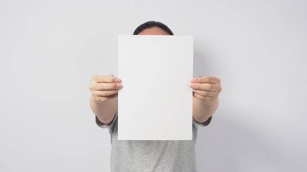 As mãos do modelo masculino estão segurando o papel a4 e usam uma camiseta cinza sobre fundo branco.