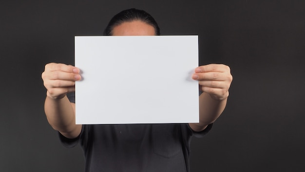 As mãos do modelo masculino estão segurando um papel a4 em branco sobre fundo preto.