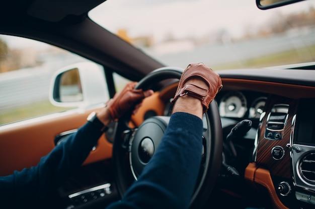 As mãos do motorista em luvas de couro, dirigindo um carro em movimento