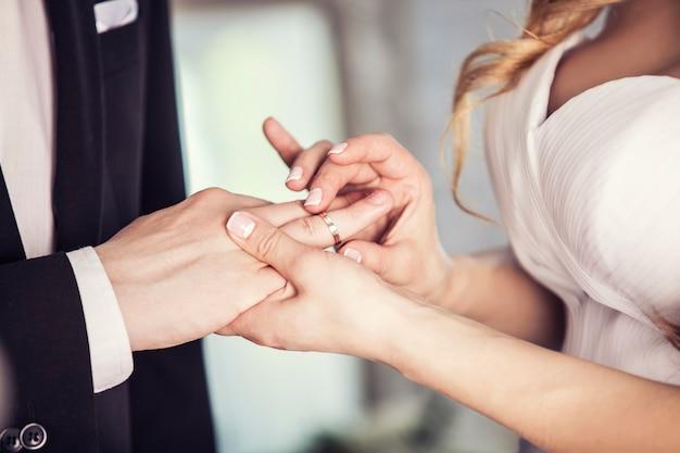 As mãos do noivo e da noiva estão usando um anel no dedo no dia da cerimônia de casamento. ouro, símbolo, religião, amor.