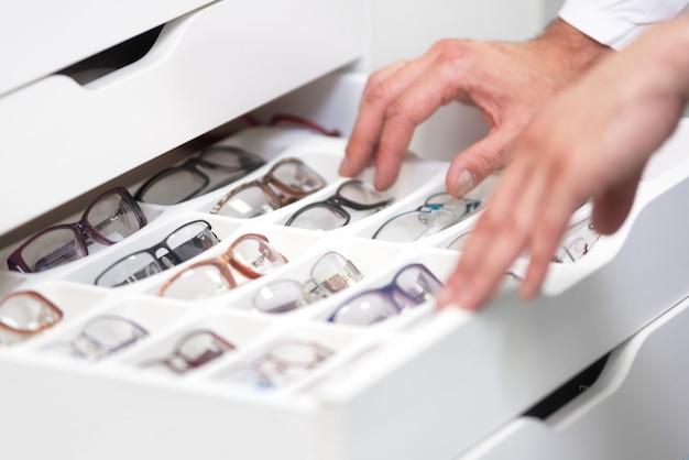 As mãos do oftalmologista fecham-se acima, escolhendo vidros de uma gaveta na loja ótica.