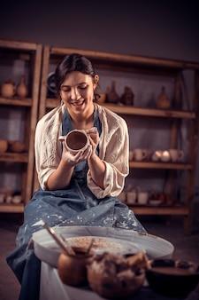 As mãos do oleiro têm a forma de uma xícara de barro. o processo de criação de cerâmica em uma roda de oleiro.