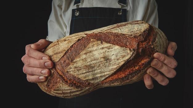 As mãos do padeiro seguram um pão oval orgânico fresco em uma parede negra