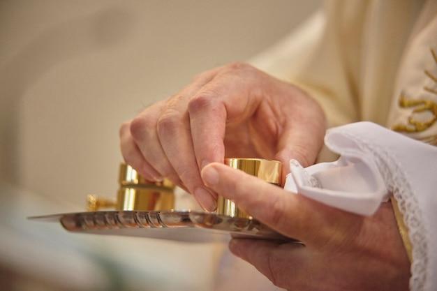 As mãos do padre segurando os recipientes de cicatrizes de cromo e catecúmenos para o rito do batismo