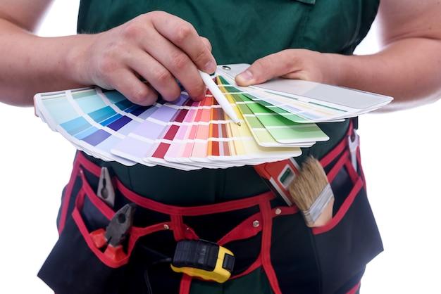 As mãos do pintor com amostra de cor em close