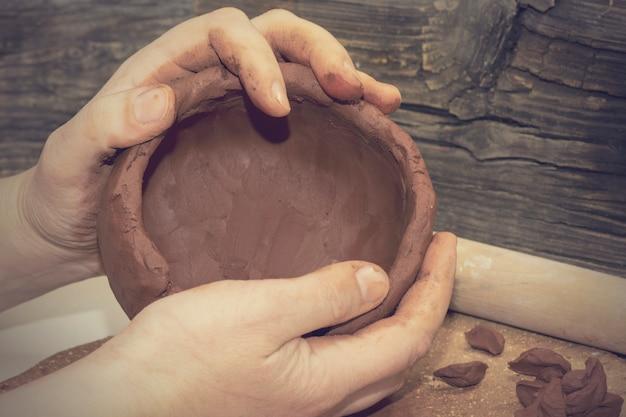 As mãos do potter moldadas de barro marrom