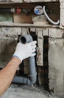 As mãos do trabalhador estão instalando canos de esgoto.