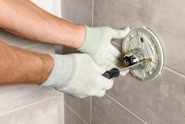 As mãos do trabalhador estão montando uma torneira embutida.