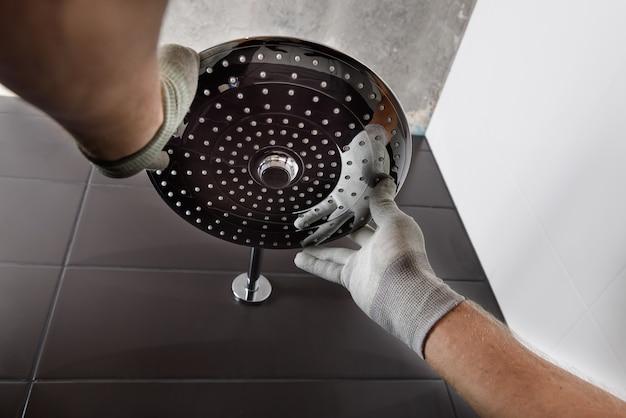 As mãos do trabalhador instalam a cabeça da torneira do chuveiro embutida